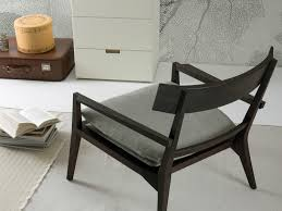 detail of annette low chair with wooden structure detail of the armrest and seat cushion