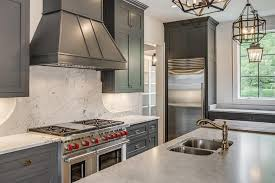 gray french kitchen hood with curved marble backsplash