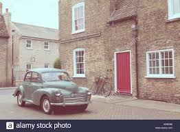 retro scene with vine british car 1950 style parked in front of victorian english building with red door matte finish