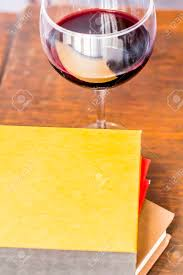 stack wine. Stack Of Books With Glass Wine In This Relaxation Themed Desk Top Stock Photo - R