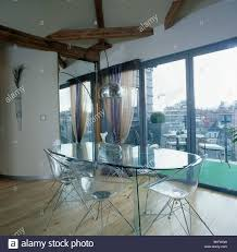 modern loft furniture. Oval Glass Table And Perspex Chairs In Modern Loft Conversion Dining Room With Doors View Of The City Furniture