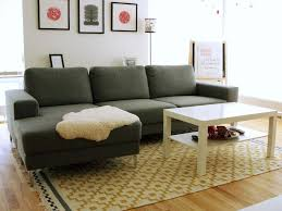 laminate floor and glossy square cream table combined with cozy grey sofa in area rug for living room