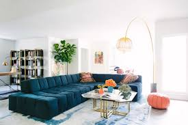short couch glass coffee table pink ottoman yellow floor lamp blue and white area rug black