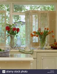 Kitchen Window Sill Red Gerberas And Orange Striped Tulips In Glass Vases On Kitchen