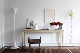 former chelsea apartment a plaster torchiere by kacper dolatowski from ferrer s gallery stands beside a neoclassical parchment console by cotton