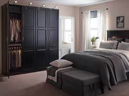 A large bedroom with a black bed and bedside tables. Shown together with a  large