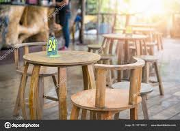 wooden round tables and chairs in old style with number inside outdoor local restaurant on morning time photo by skasiansin
