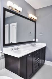 lighting bathroom mirror. bathroom grey wall and dark cabinet with light fixtures over mirror lighting