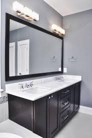 bathroom grey wall and dark cabinet with bathroom light fixtures over mirror