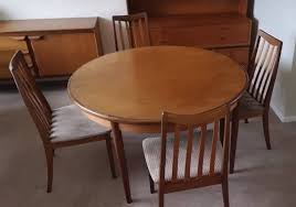 solid teak extendable round dining room table with four chairs extends to six seater