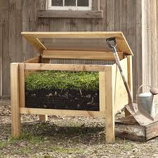 above a solar assist composter with a frame of western red cedar has mesh side panels to increase air flow and a corrugated poly cover to let in sunlight