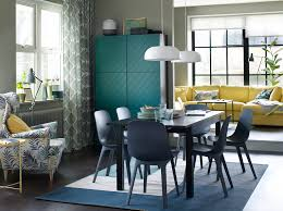a blue brown and green dining room setting with a yellow sofa in the background chair