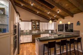 classic half vaulted ceiling kitchen design with track lighting and cabinet with marble countertop ideas