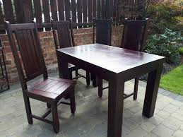 solid dark wood dining table and 4 chairs