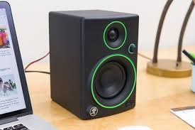 awesome computer speakers. a black mackie cr3 computer speaker with green detail sitting next to macbook. awesome speakers