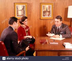 man interviewing couple at desk in office interview 1960 1960s indoor bank loan insurance woman