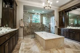 master bathroom with center bathtub and dark marble wood cabinets with large glass shower