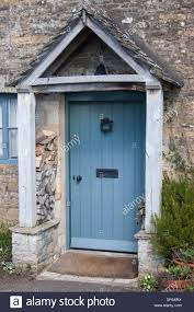 Traditional stone cottage front door in the Cotswolds village of Lower  Slaughter