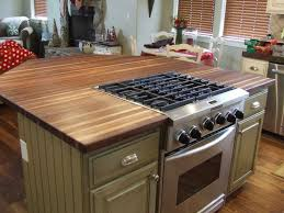 Wooden Kitchen Island With Modern Stove Top On Glossy Brown Marble .