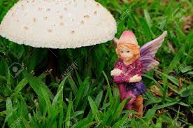 a fairy figurine sitting next to a mushroom in the garden stock photo 91986667