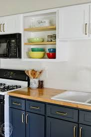 love the dark blue with the butcher block countertops and the white upper cabinets this