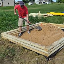 a man smoothes out sand in a new sandbox