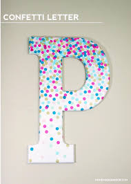 make some diy wall art by decorating a letter with confetti this is perfect for