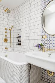 gorgeous bathroom features a bathtub shower combo clad in white hex tiles under a a white square tiled surround installed in a brick pattern lined with a