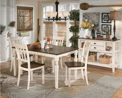 square dark wood top and white legs of dining table cream wall
