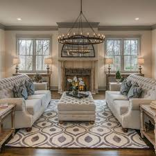 This living room boasts an oversized chandelier and a fireplace with well  staged furniture making this