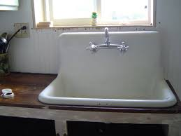white old kitchen sink made of ceramic material and stainless