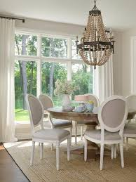 dining room with white curtains neutral chandelier and white chairs