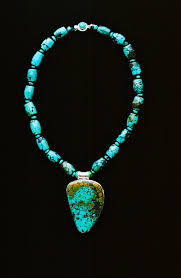 teardrop shaped blue green matrix veined turqoise pendant set in silver on necklace of barrel shaped matching turquoise beads rondelles