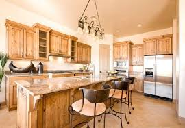 A Maple Wood Kitchen With A Long Eat In Kitchen Island And Light Cream Walls