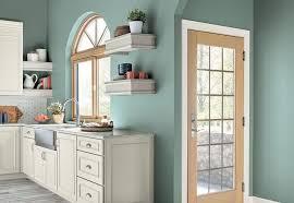 cocina con muebles crema y paredes verde azulado