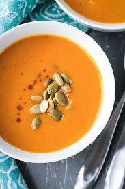 bowl of ernut squash apple soup topped with roasted pumpkin seeds and a few splashes of
