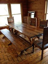 old long narrow dining table on brick floor inside glass window in wooden wall