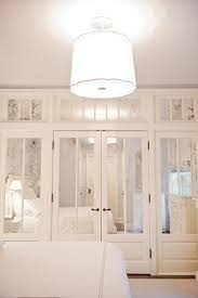 gorgeous monochromatic bedroom with barbara barry simple scallop pendant and wall of antiqued mirrored closet doors