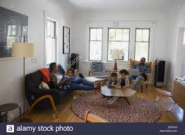 Relaxing Living Room Family Relaxing And Using Technology In Living Room Stock Photo