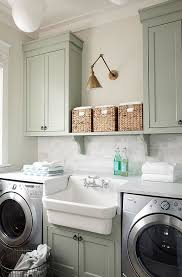 lighting for laundry room. laundry room cabinet paint color paired with white marble countertop and brass lighting for