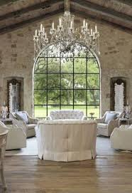 a vintage living room with white fabric furniture and an oversized vintage chandelier with hanging crystals