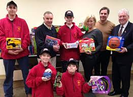 helping to deliver gifts collected by boy scout 90 for distribution to foster children through
