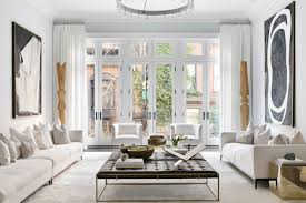 apartment with white walls white couches leather ottoman and coffee table book