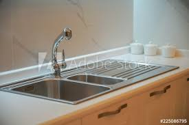 stainless sink washbasin and faucet on a modern kitchen countertop