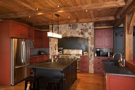 Here's another lush, rustic styled kitchen, with dark red stained cabinetry  under black marble