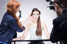 shot of a make up preparing a model for a photo shoot stock photo