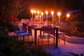 decorated garden table with flaming torches in the evening light bavaria germany