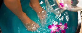 feet in a large water filled basin with floating fuchsia orchids as more water pours