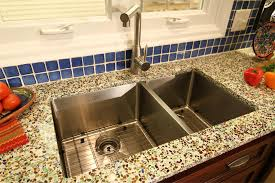 pretty double groumet undermount sink with white recycled glass countertops added blue ceramic backsplash in open view kitchen designs