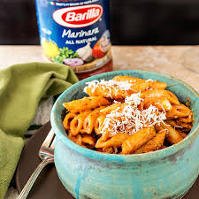 3 4 shot of penne pasta in a creamy sauce in a blue bowl with